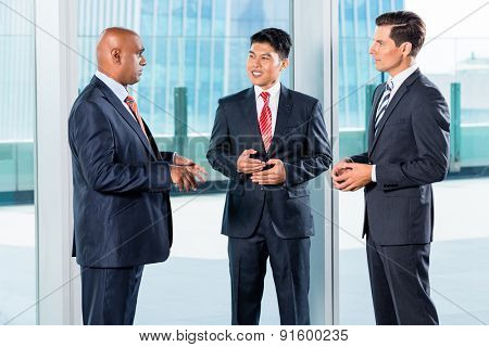 Multi ethnic business team reporting to Indian CEO discussing in front of city skyline