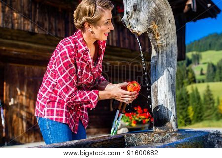 Woman drinking from well in front of mountain cabin