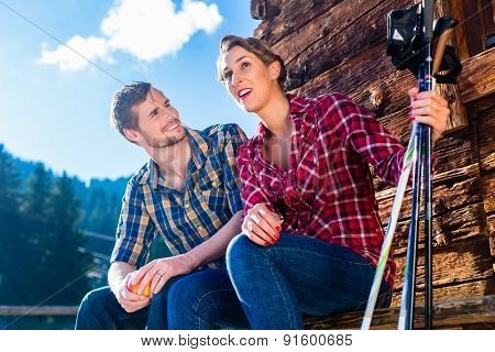 Couple resting from Nordic walking fitness exercise in mountain cabin