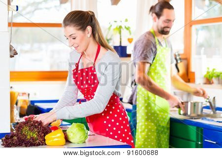 Man and woman preparing healthy meal in domestic kitchen at home