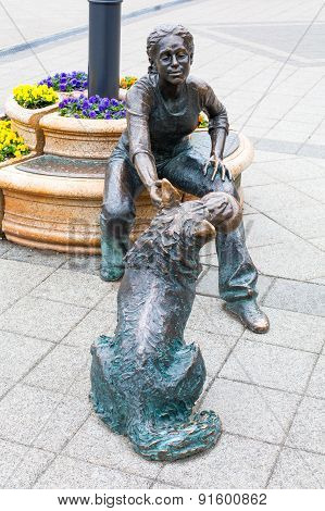 Bronze statue of a girl playing with her dog next to the River Danube.