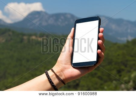Hand Holding Smart Phone On Hill