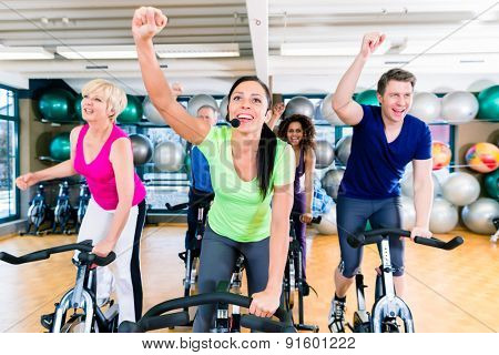 Group of men and women spinning on fitness bikes in gym, diversity people, old, young, black and white