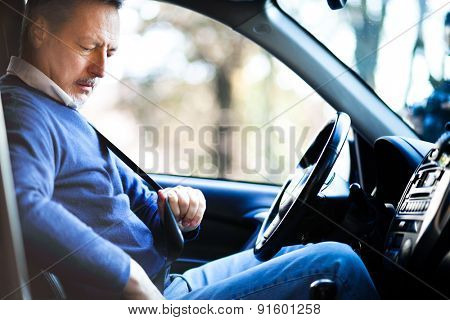 Man fastening safety bealt in his car