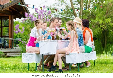 Family and neighbors at garden party drinking, sitting in front of a home with friends and family