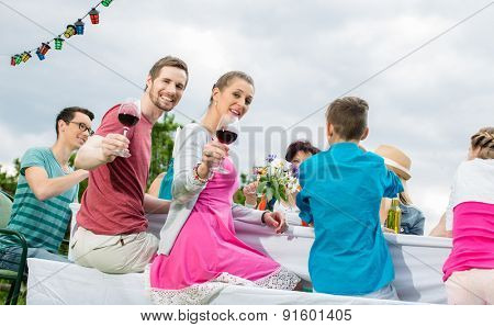 Couple toasting with wine at garden party with friends and family