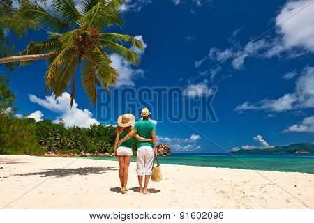 Couple relaxing on a tropical beach at Seychelles, La Digue.