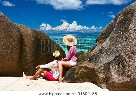 Couple relaxing among granite rocks on a tropical beach Anse Source d'Argent at Seychelles, La Digue.