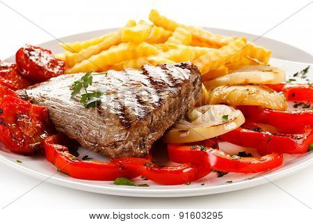 Grilled steak, French fries and vegetables on white background