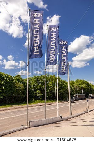 The Flags With Hyundai Dealership Sign Over Blue Sky