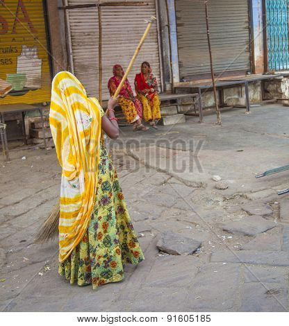 Indian Women Of Fourt Class In Brightly Colored Clothing Cleans The Street