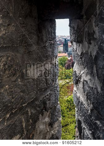 Charles Bridge seen through fortified wall embrasure, Prague, Czech Republic