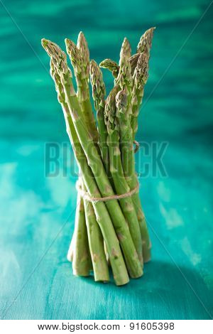 bunch of fresh asparagus on turquoise background