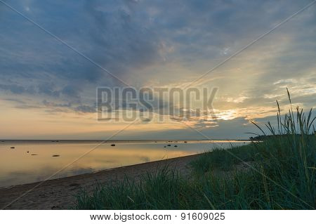 Calm And Colourful Cloudscape Sunrise At Sea Gulf With Tall Grass On Beach