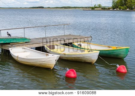Three Rowboats At Wooden Dock In Sea Bay