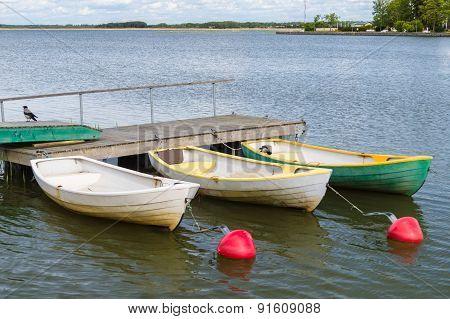 Three Rowboats At Wooden Dock In Sea Bay