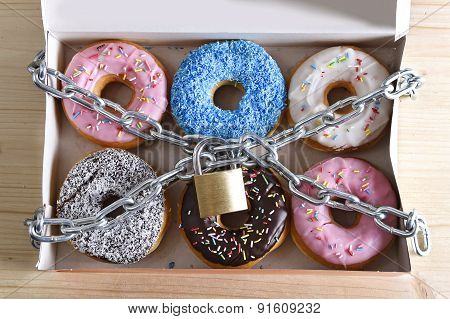 Box Full Of Tempting Delicious Donuts Wrapped In Metal Chain And Lock In Sugar And Sweet Addiction