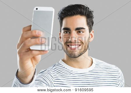 Handsome young man making a selfie picture with phone, isolated over gray background