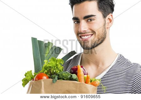 Handsome young man carrying a bag full of vegetables, isolated over white background