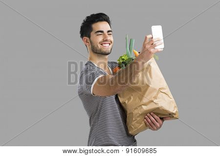 Handsome young man carrying a bag full of vegetables and making a selfie, isolated over gray background