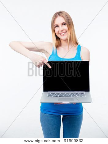 Smiling young woman pointing finger on the blank laptop screen isolated on a white background. Looking at camera