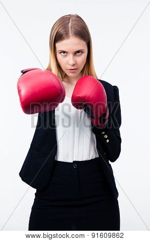 Portrait of a businesswoman in boxing gloves over gray background. Hitting on camera