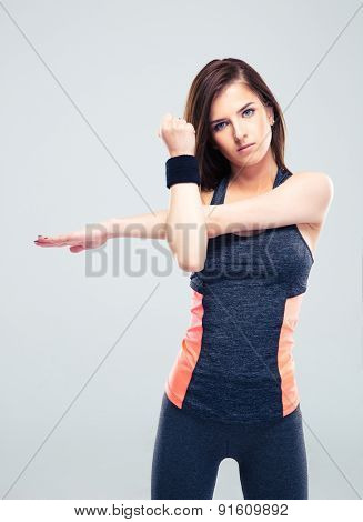 Cute fitness woman stretching hands over gray background
