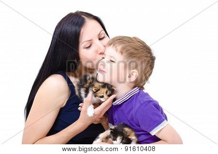 Loving mother kisses son, holding two tricolor kittens