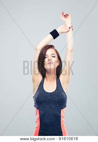Pretty sports woman stretching hands on gray background and looking at camera