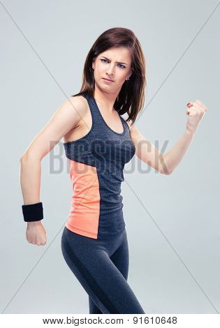 Funny fitness woman posing on gray background and looking at camera