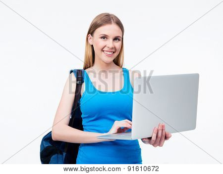 Happy casual woman with backpack standing and using laptop isolated on a white background. Looking at camera