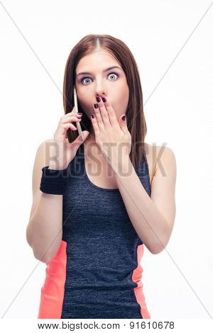 Surprised young fitness woman talking on the phone isolated on a white background. Looking at camera