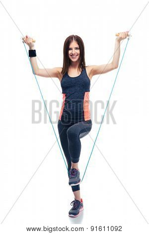 Full length portrait of a smiling sporty woman standing with jumping rope isolated on a white background. Looking at camera
