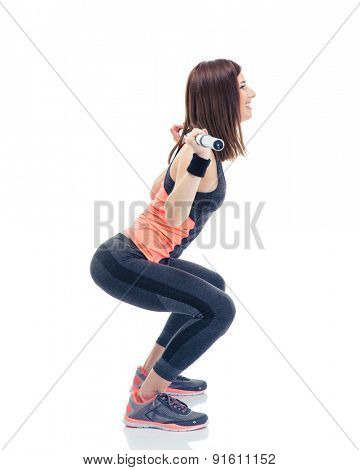 Side view portrait of a fitness woman doing squatting with barbell isolated on a white background