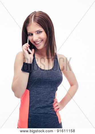 Smiling fitness cute woman talking on the phone isolated on a white background and looking at camera
