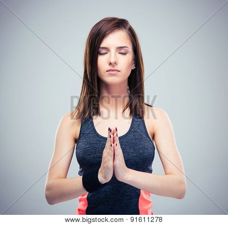 Fitness pretty young woman with hands together in meditation over gray background.