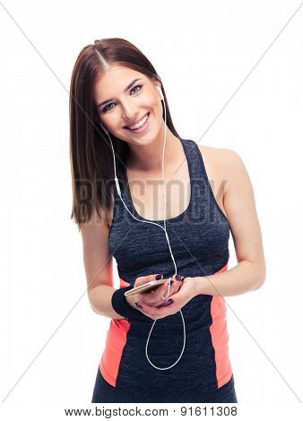 Happy sports woman in headphones holding smartphone and looking at camera. Isolated on a white background