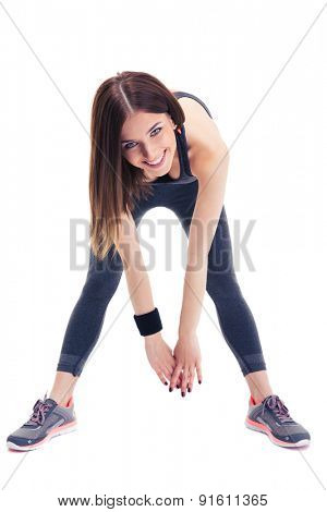 Cheerful sporty woman doing stretching exercise isolated on a white background. Looking at camera