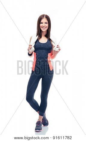 Full length portrait of a smiling fitness woman holding towel isolated on a white background. Looking at camera