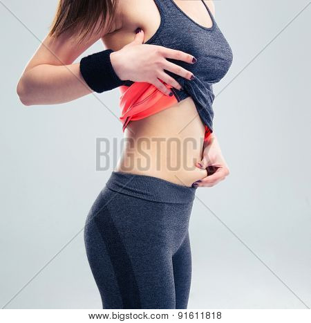 Closeup portrait of a fitness woman pinch a fat on her abdomen on gray background