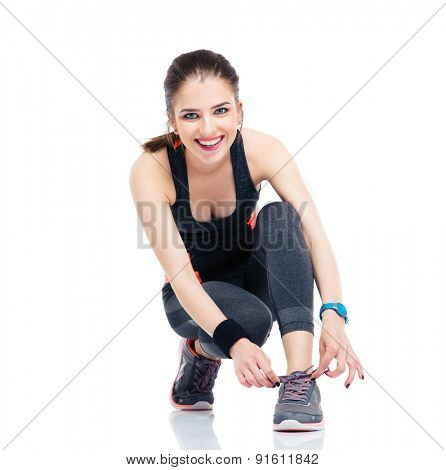 Fitness woman in sports clothes tying shoelaces isolated on a white background. Looking at camera