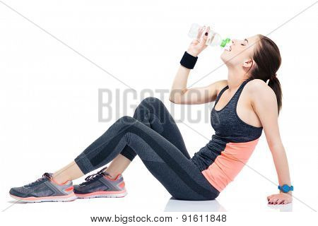 Woman sitting on the floor and drinking water isolated on a white background