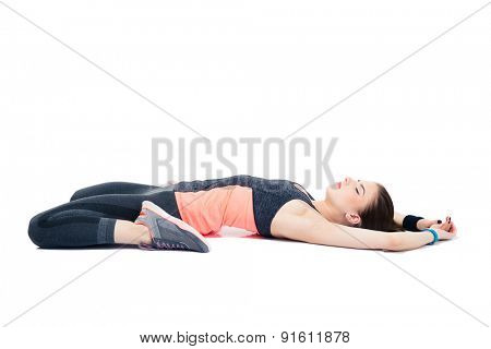Sporty woman lying on the floor and stretching isolated on a white background