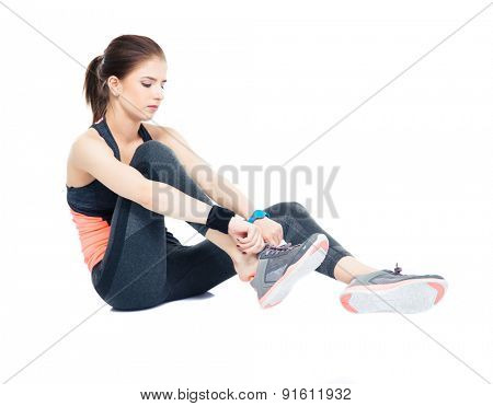 Sporty woman puts on her sneakers isolated on a white background