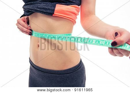 Closeup image of a woman measuring her tummy with a measuring tape isolated on a white background