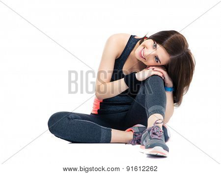 Smiling sports woman resting on the floor isolated on a white background. Looking at camera