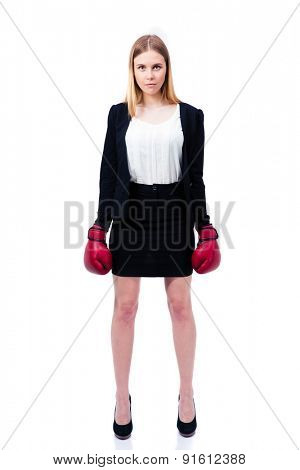 Full length portrait of a young businesswoman standing in suit and boxing gloves over white background. Looking at camera