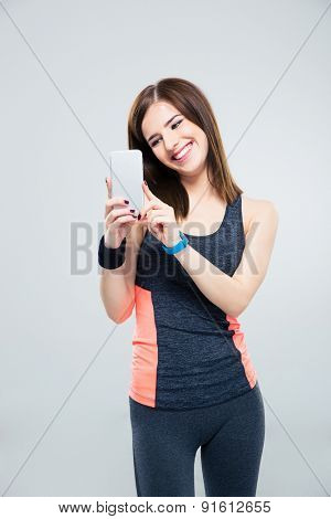 Fitness woman using smartphone over gray background