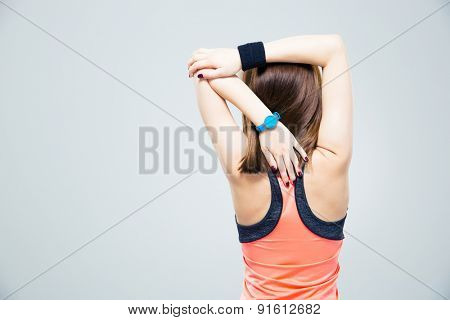 Back view portrait of a fitness woman stretching hands over gray background
