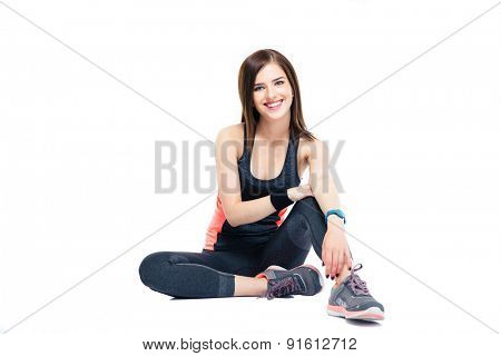 happy sports woman sitting on the floor isolated on a white background. Looking at camera